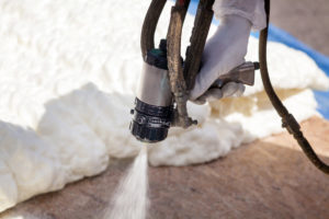 Technician spraying foam insulation using Plural Component Spray Gun